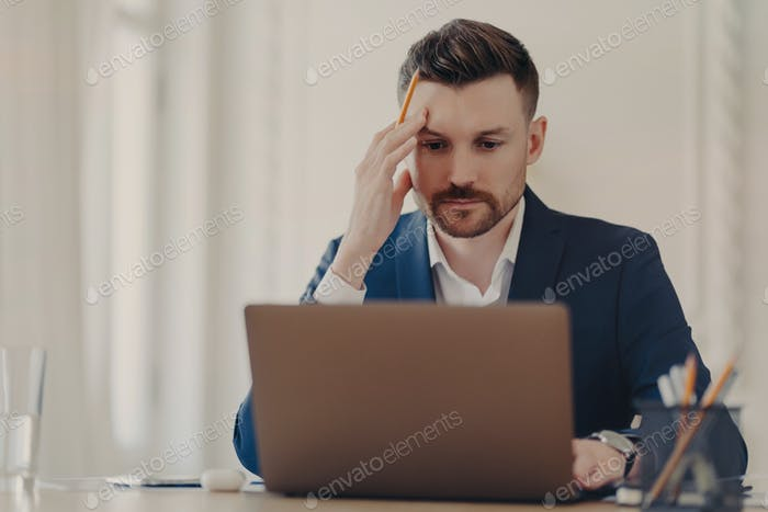 Thinking business executive sitting at his desk in front of laptop