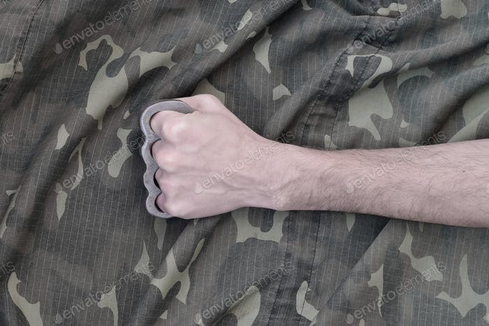 Male fist with brass knuckles on the background of a camouflage