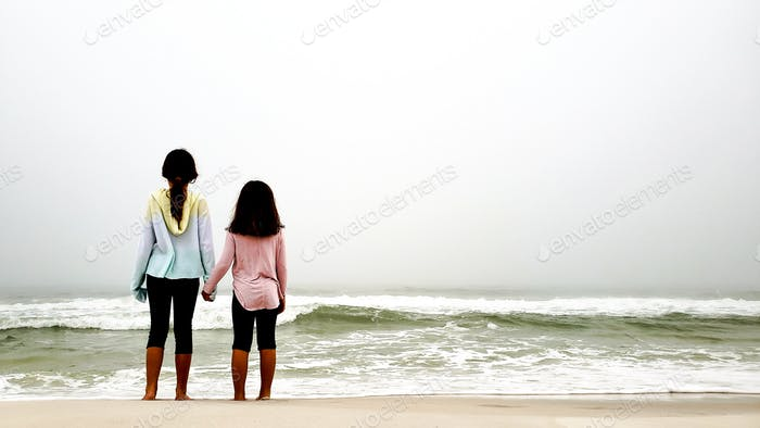 Two sisters in a fog staring at ocean waves hoping water is warm enough to enter without freezing in