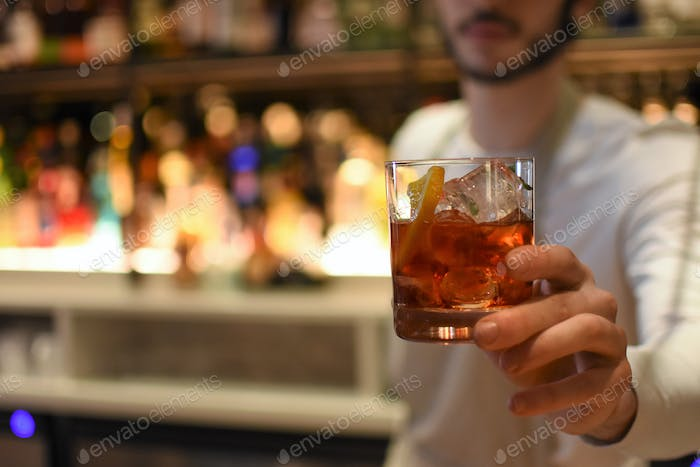 Midsection of a Bartender handing over a negroni