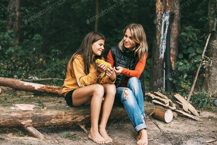 Una adolescente con su madre está sentada en un tronco en el bosque, una niña come maíz, hace senderismo