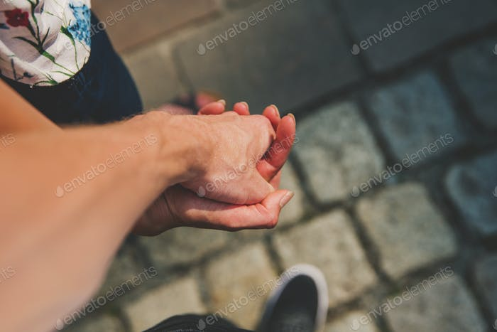 Two young lovers are holding their hand on the town's square