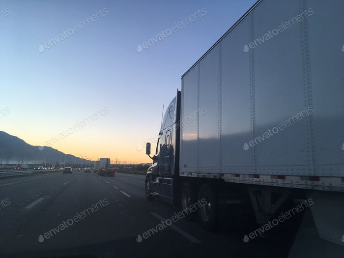 Big truck on freeway with sunset and mountains