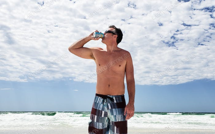 Generation X man with a love my body mentality drinking beer on the beach during vacation...