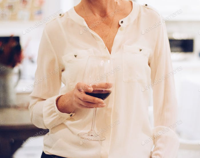 Woman is holding a glass with red wine.