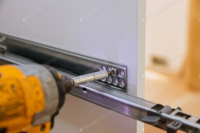 Handyman service in the process of assembling furniture kitchen cabinets screwdriver and mounting