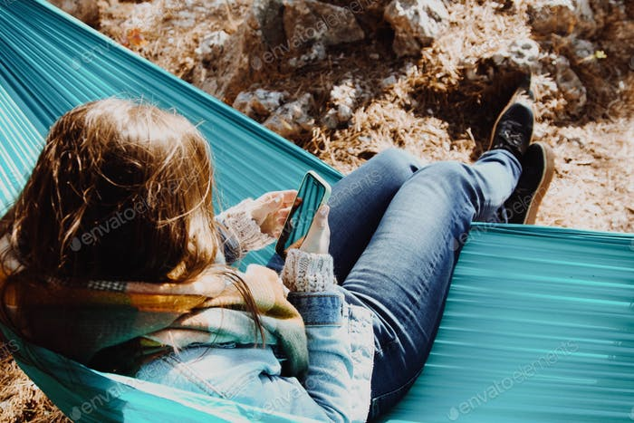 young woman sitting in a hammock uses a mobile phone  Nominated