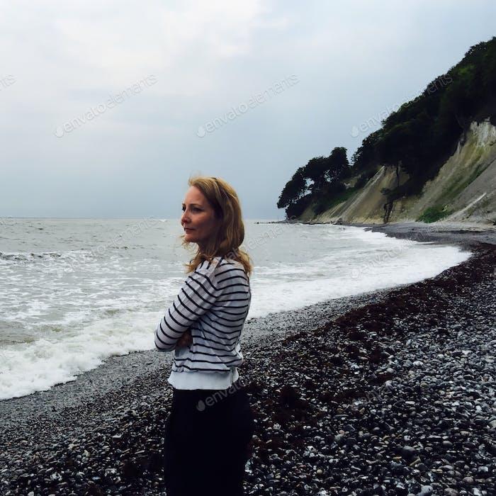 Frau reflektiert am Strand.
