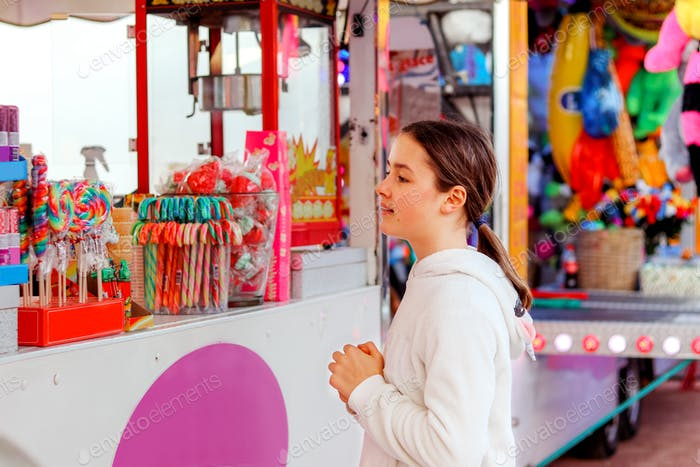 Cute tween girl looking with desire at bright colorful sugar candies and lollypops trying to choose