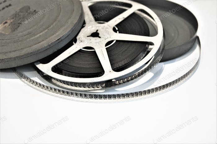 Old vintage movie reel and canister on bright white background