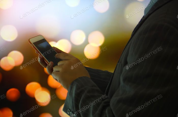 Business people texting on mobile phone screen against bokeh light background