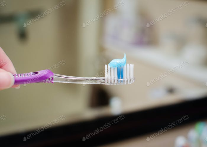 Hand hält eine Zahnbürste und Zahnpasta im Badezimmer, Zahnpflege, Zähne putzen