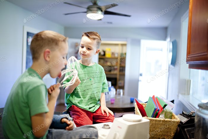 two boys licking the batter off of mixing whisks