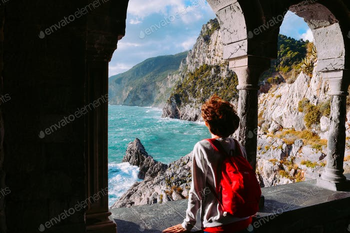 Female tourist with pink backpack looking at the beauty of Mediterranean sea at Cinque Terre