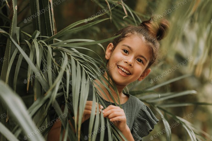 The face of a little girl surrounded by tropical leaves. Closeup portrait of  beautiful swarthy baby