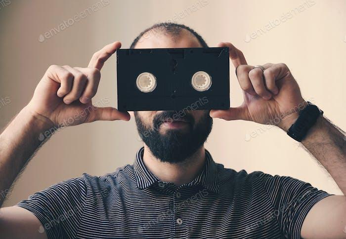 Man holding a video cassette