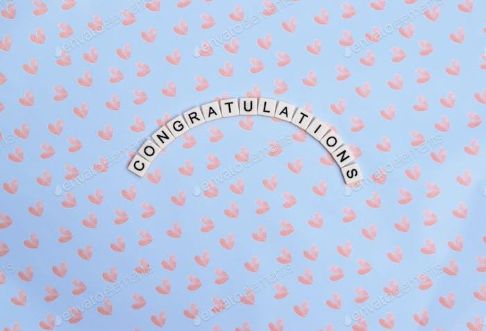 Glückwünsche in schwarzen Buchstaben auf hellblauem Hintergrund mit rosa Herzen buchstabiert