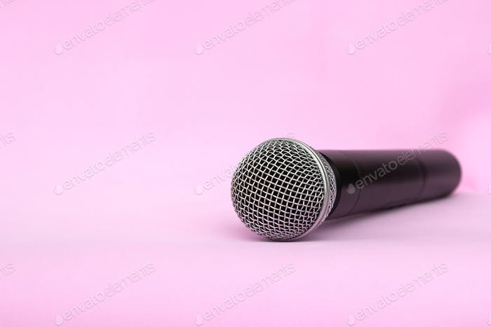 Vocal silver microphone wireless for audio recordings, karaoke on pink background