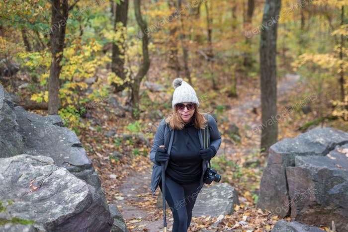 Woman hiking up bluffs at Devils lake state Park in Autumn