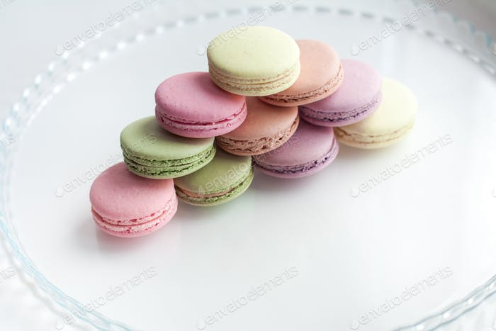 Colorful macaroons built in pyramid on glass plate