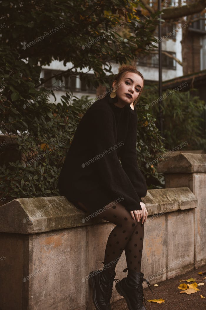Woman with autumn sweather sitting. Moody and rainy autumn