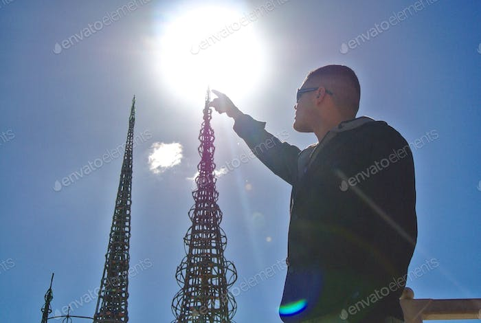 Perspective shows young man touching the top of a sculpture at The Watts Towers.
