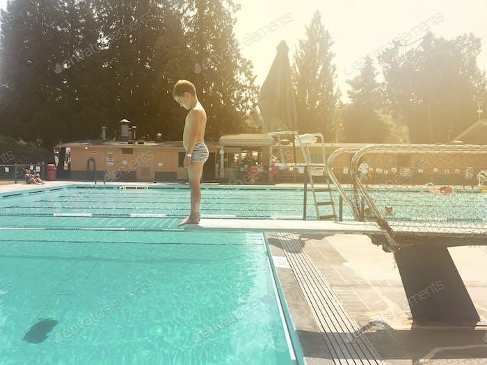A little boy stands contemplating jumping off a diving board at  neighbourhood pool.