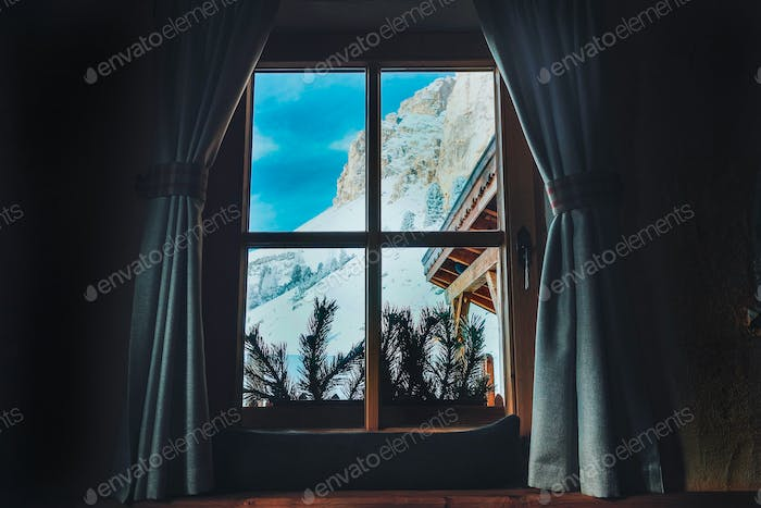 A mountain view through a window in a wooden chalet