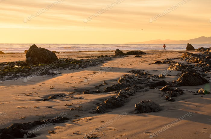Person walks along a rocky coastline at sunset