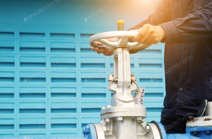 Nahaufnahme eines Mannes Hände Betätigen eines Regelventils auf dem Wasserhahn installiert
