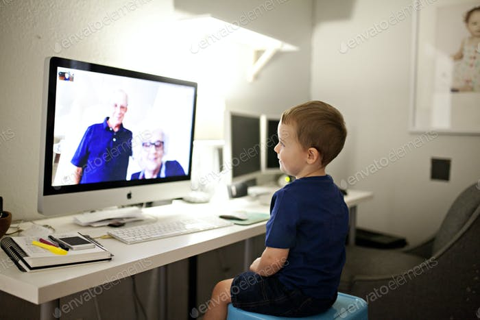 kids laughing and talking to grandparents via the internet on facebook