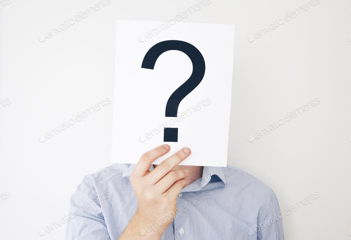 A man wearing a light blue shirt holding a question mark in front of his head