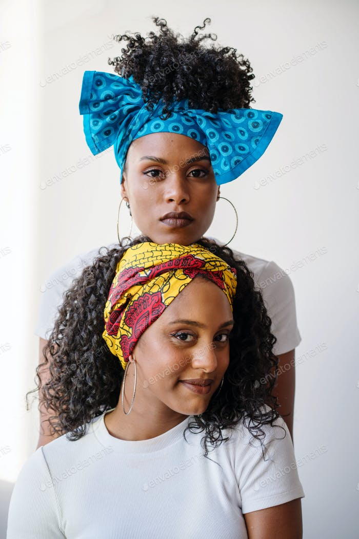 Two young Beautiful African woman with dark skin wearing traditional head scarfs