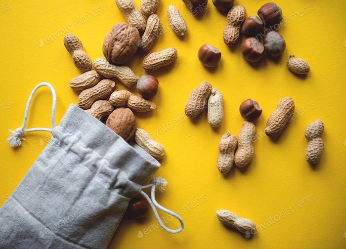 Umweltfreundliche Stofftasche mit Erdnüssen und Haselnüssen auf gelbem Hintergrund