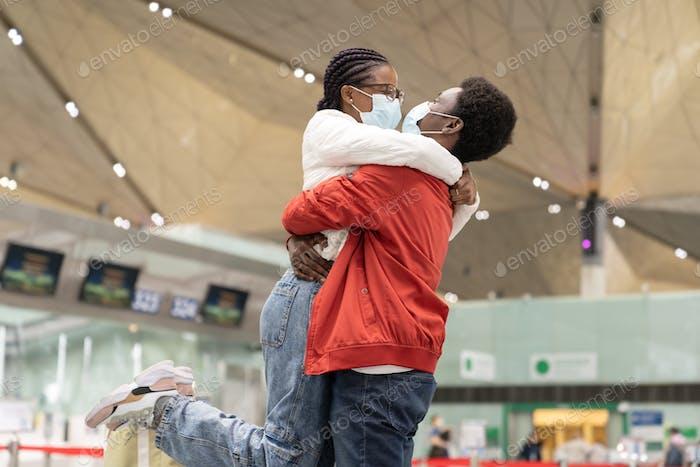 Reunión de parejas africanas bajo Covid-19 nueva normalidad. Hombre y mujer alegre en máscaras abrazo en el aeropuerto