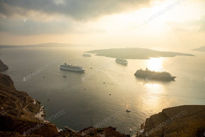 Amazing evening view from Fira on cruise ships at sunset, Santorini in Greece