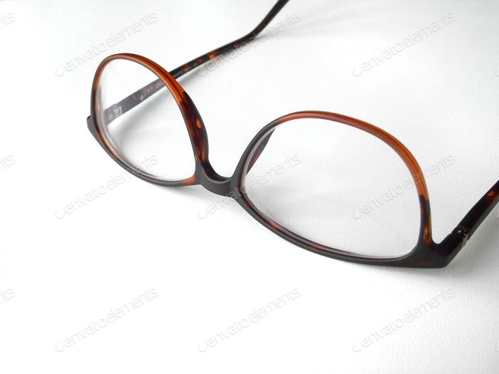 Close up shot of a pair of reading glasses on a white background
