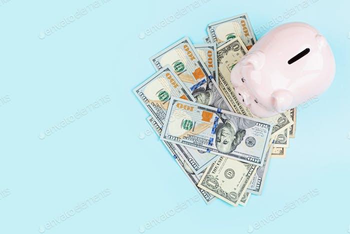 Hucha con dinero en efectivo dólares sobre fondo azul