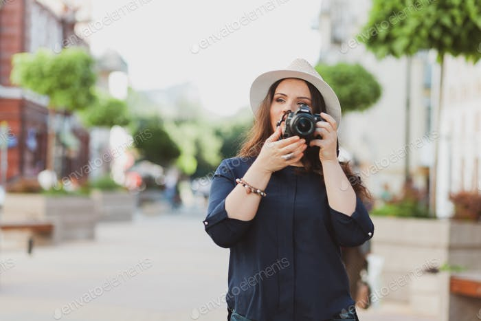 beautiful woman photographer travels around the city and takes pictures