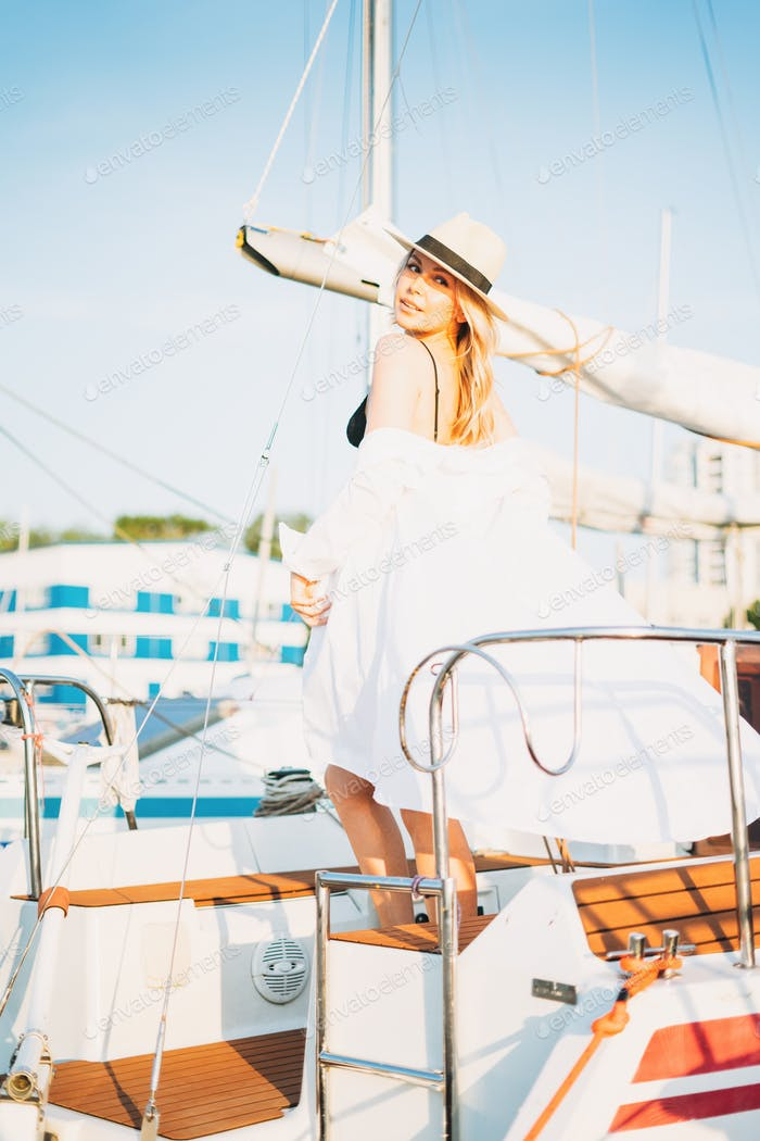 Beautiful sensitive blonde young woman in short and straw hats on the yacht at pier