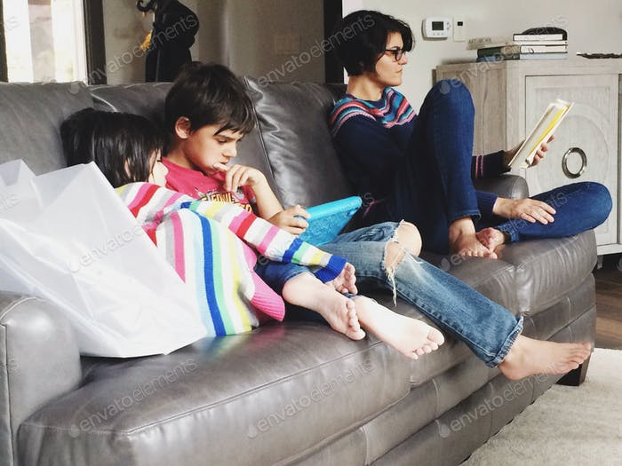 Crianças usando dispositivos e mãe lendo um livro