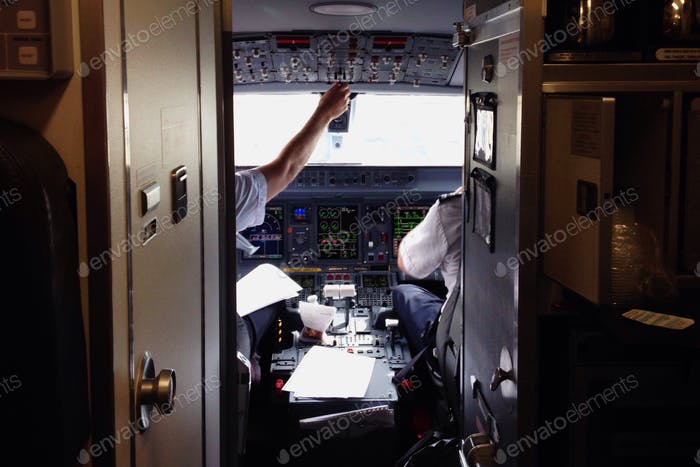 Pilots in the cockpit of an airplane are visible while boarding.