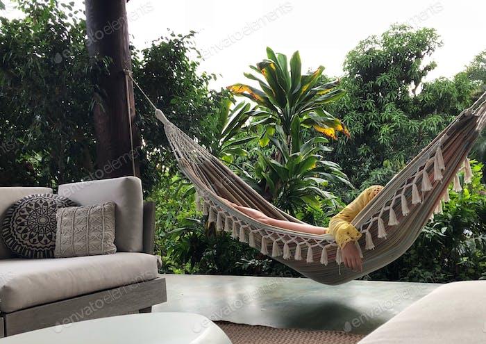 Mujer el Relajante en una hamaca en el entorno tropical