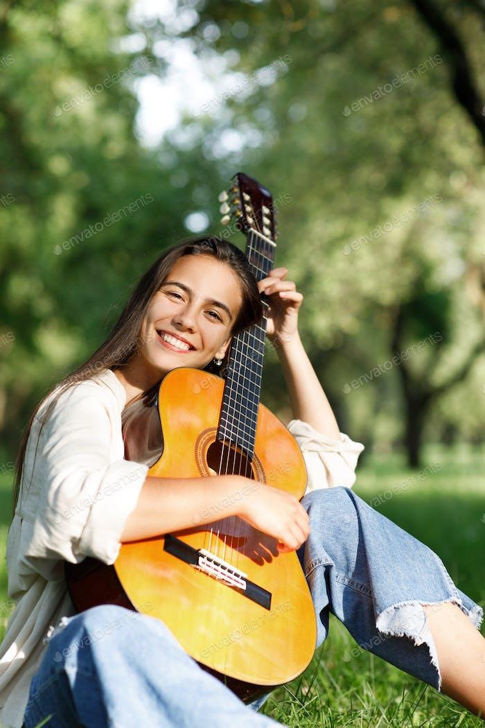 Porträt einer jungen Gitarristin, die lächelt und eine Gitarre in den Händen hält. Musikerin, Musik.