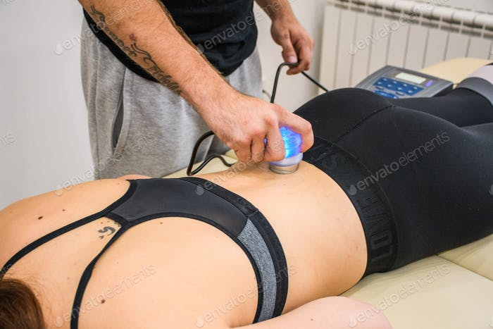 Hand holding a blue ultrasound probe on woman's back