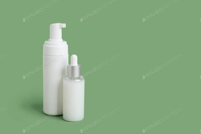 Foam container and bottle with serum on a green background. White clean tubes with copyspace. Mockup