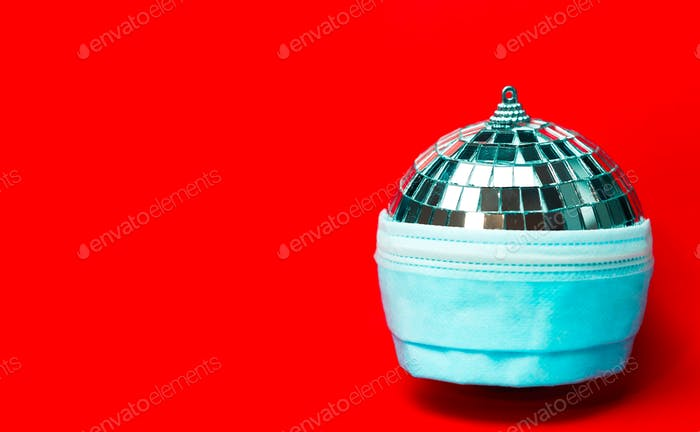 disco ball in respiratory protective face mask on red background