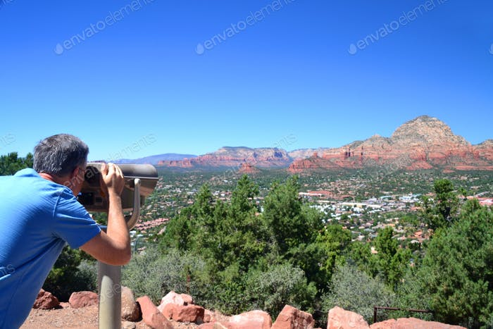 A man looking through a roadside scenic viewfinder