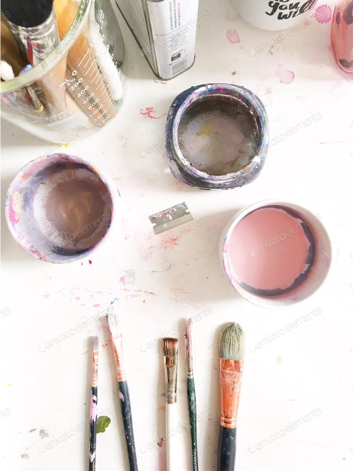 Looking down at an artist's tools and dirty water bowls on a messy white desk.