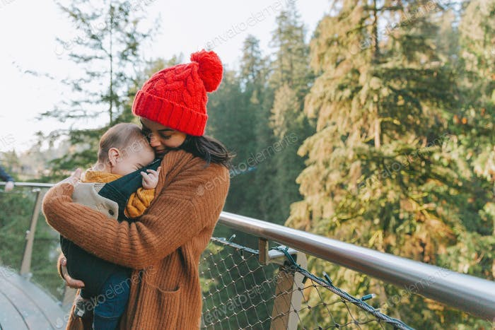 A mother snuggling her baby in a carrier on a bridge in the forest.